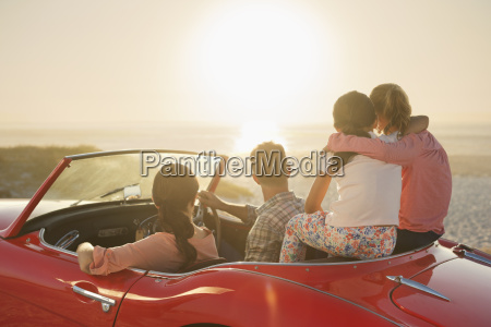 family watching sunset over ocean from