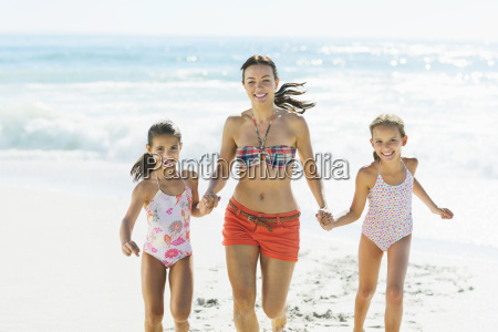 mother and daughters holding hands and