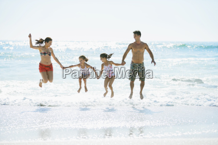family jumping in waves on beach