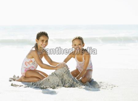girls making sandcastle on beach
