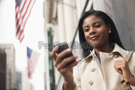 businesswoman using cell phone on city