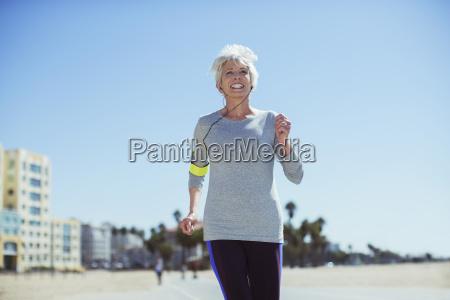 senior woman power walking on beach
