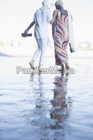 women walking barefoot on beach
