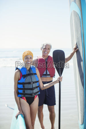 portrait of senior couple with paddleboards