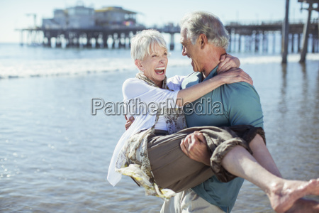 senior man carrying wife on sunny