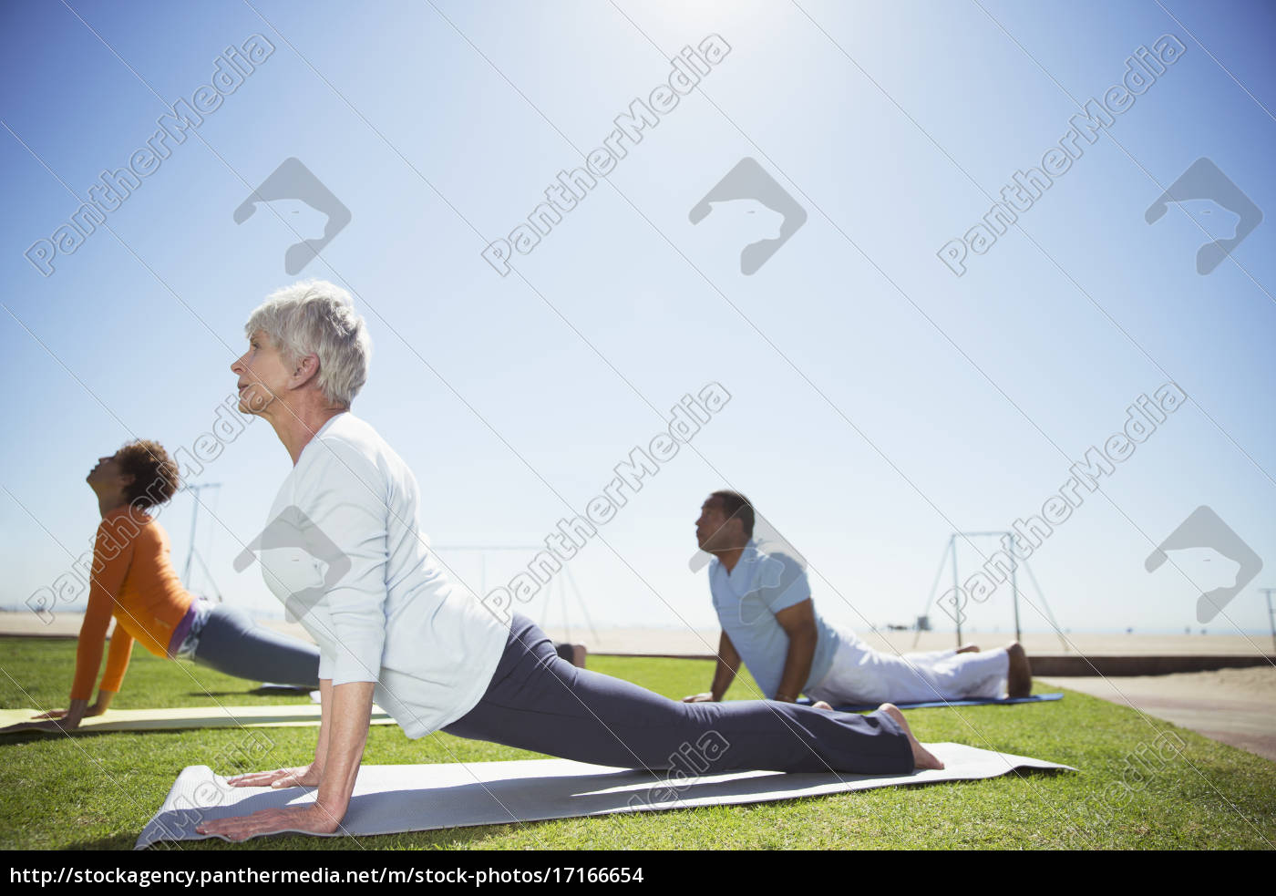 seniors, practicing, yoga, in, sunny, beach - 17166654