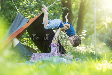 father and son playing near camping