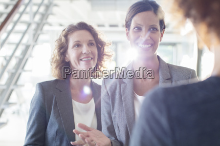 three smiling businesswomen talking in office