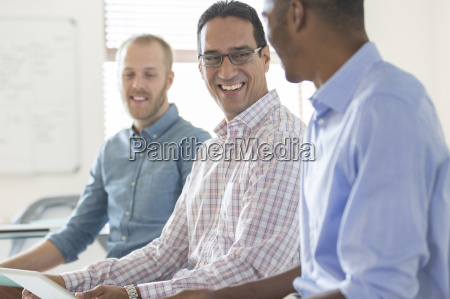three smiling men working together in