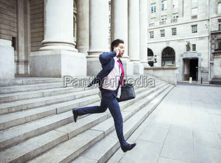 businessman on cell phone running on