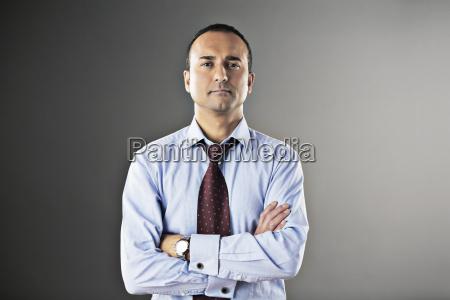 portrait of confident businessman with arms
