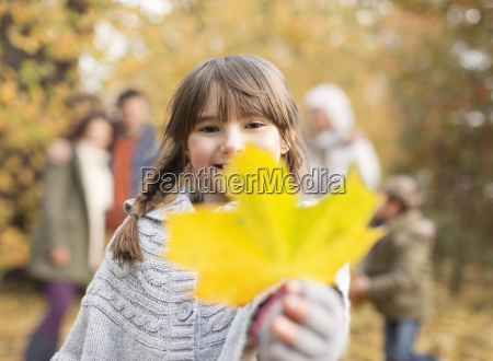 girl holding autumn leaf in park