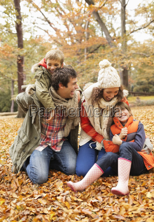 family playing together in autumn leaves