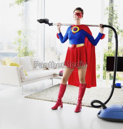superhero holding vacuum in living room