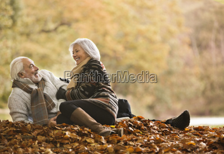 older couple sitting in autumn leaves