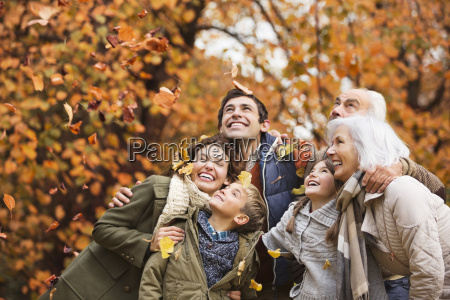 family playing in autumn leaves in