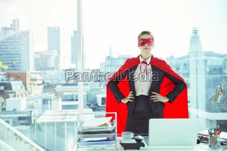 businesswoman wearing cape and mask in