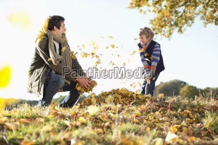 father and son playing in autumn