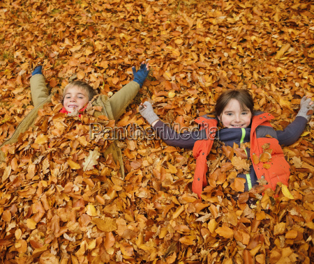 children laying in autumn leaves