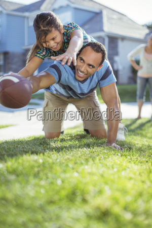 father and daughter playing football in