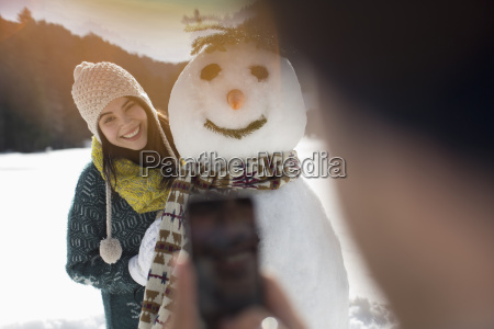 man photographing woman with snowman