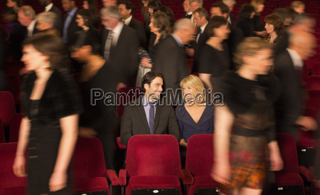 couple sitting among people leaving theater