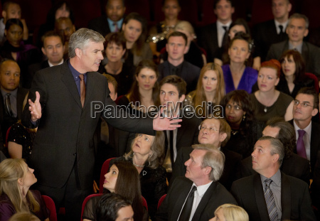 theater audience watching standing man gesturing