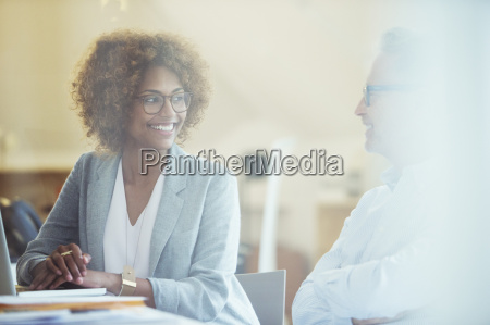 two office workers talking at desk
