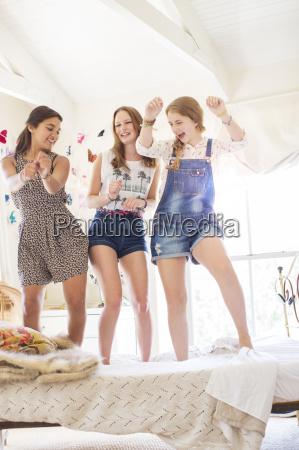three teenage girls dancing on bed