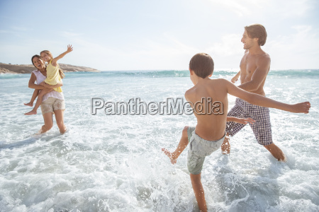 family playing together in waves on