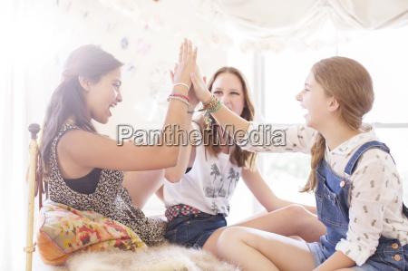 three teenage girls doing high five