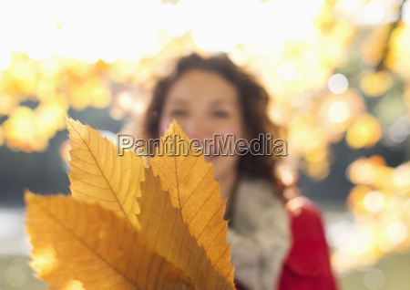 woman holding autumn leaves in park
