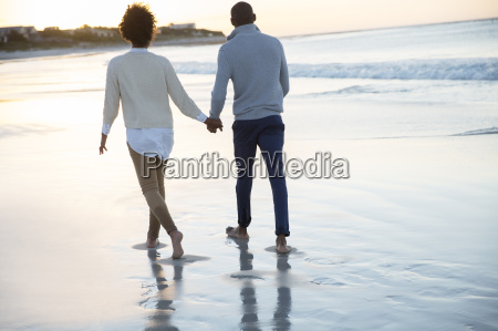 young couple holding hands and walking
