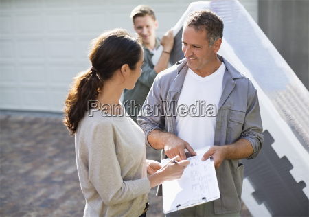 woman signing for package in driveway