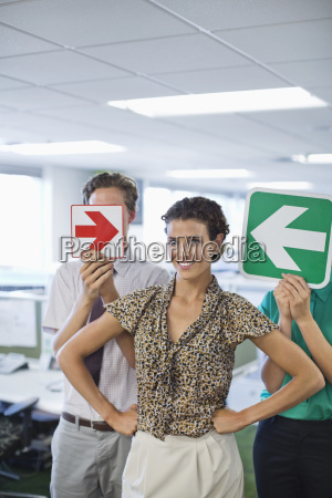 business people holding arrows in office
