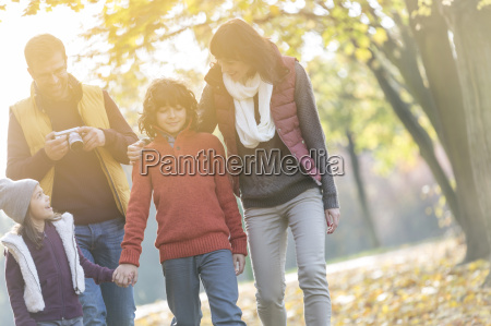 family with camera walking in sunny