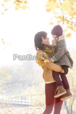 mother holding daughter in sunny autumn
