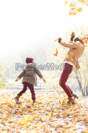 playful mother and daughter throwing autumn