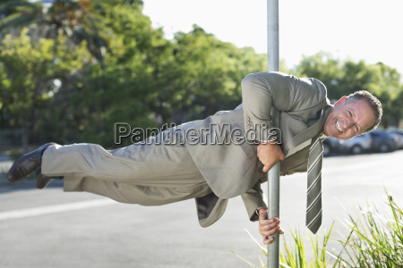 businessman balancing on pole on city