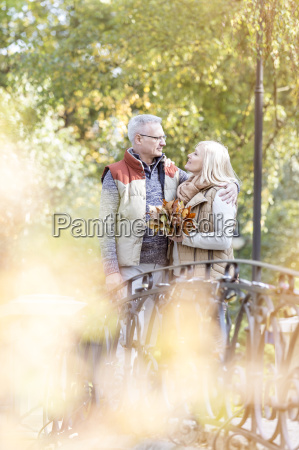 senior couple with autumn leaves hugging