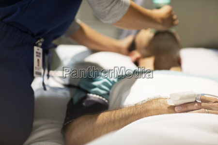 doctor holding oxygen mask over male