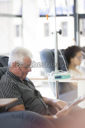 man reading magazine undergoing medical treatment