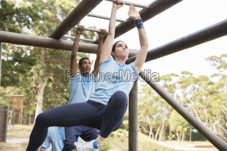 determined woman swinging on monkey bars