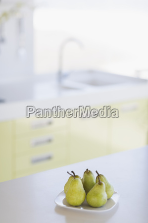 plate of pears on kitchen counter