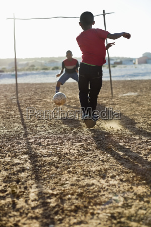 boys playing soccer together in dirt