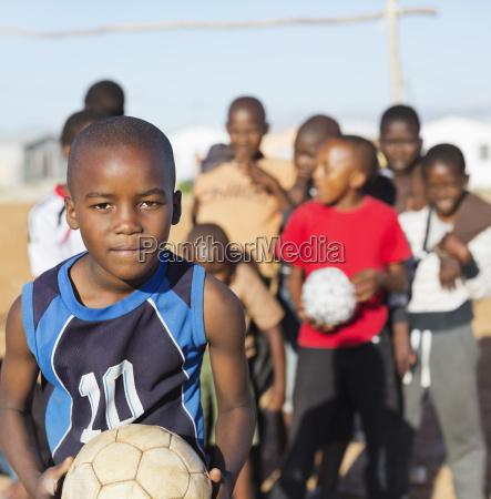 boys holding soccer balls in dirt