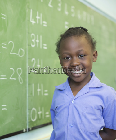 student smiling at chalkboard