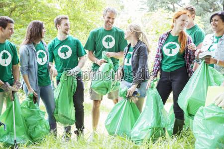 smiling environmentalist volunteers picking up trash