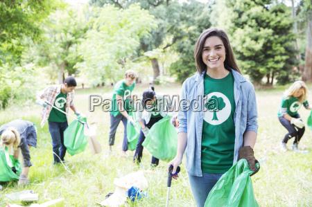 portrait of smiling environmentalist volunteer picking