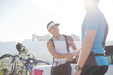 cyclists shaking hands on rural road